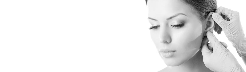 korekta uszu - lekarz bada ucho pacjentki przed zabiegiem
