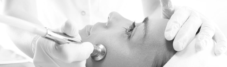 mikrodermabrazja diamentowa - kosmetyczka wykonuje zabieg na twarzy pacjentki specjalnym urządzeniem
