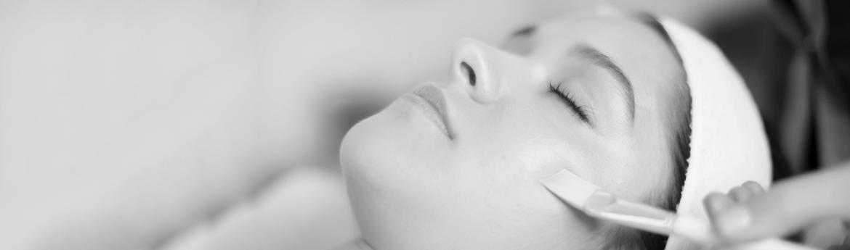 peeling medyczny - kosmetyczka nakłada preparat pędzelkiem na twarz pacjentki