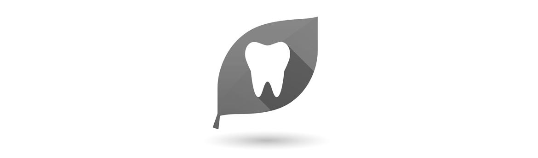leczenie biologiczne zęba - symbol zęba na tle zielonego liścia